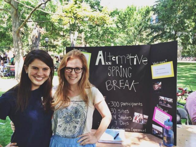 Students posing in front of Alternative Spring Break table at Festifall