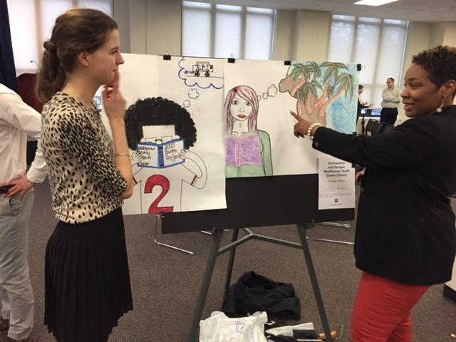 Photo of student and community partner looking at poster created by literacy program at Washtenaw County Youth Center.