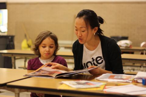 Student reading with child