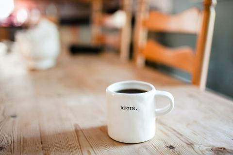 White mug with the word begin in typed text on it, on a blurred wood table with chairs
