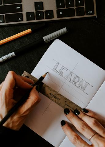 two hands drawing the word LEARN on a notebook using a ruler beneath the word, with keyboard, pen and pencil on the top edge of the frame
