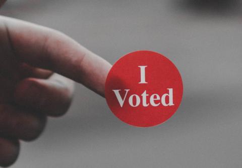 I voted sticker on a person's finger by Parker Johnson on Unsplash