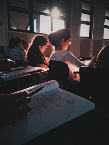 Students sitting at desks in a sun-filled classroom