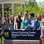 Students around Ginsberg Center sign