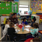 student working with children at a table
