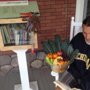 Student with basket of vegetables next to Little Free Library