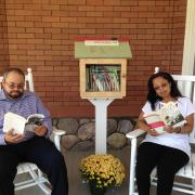two people reading next to Little Free Library