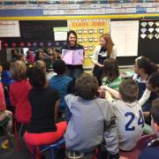 students reading to children