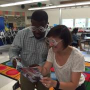 Two individuals wearing silly glasses preparing for book distribution