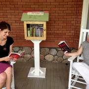 Ginsberg Center staff reading at the Little Free Library