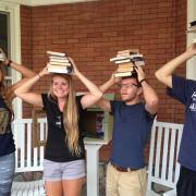 students with books on their heads