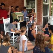 Students sitting with Little Free Library
