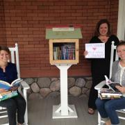 Students posing with Little Free Library