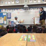 two students reading to children
